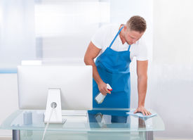 stock photo of disinfection  - Handsome young janitor or cleaner cleaning an office spraying the top of the desk with disinfectant before the office workers start their day - JPG