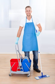 stock photo of disinfection  - Janitor cleaning wooden floors with a mop and a cart with two buckets for the disinfectant and water pausing to smile at the camera as he goes about his work in an office building - JPG