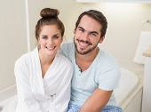 Young couple smiling at the camera at home in the bathroom