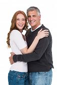 Casual couple smiling at camera on white background