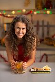 Happy Young Woman Drinking Tea In Christmas Decorated Kitchen