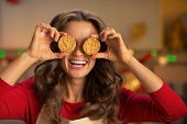 Portrait Of Happy Young Housewife Holding Cookies In Front Of Ey