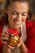 Portrait Of Happy Young Housewife Holding Jar With Honey Nuts