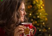 Portrait Of Happy Young Woman Eating Christmas Snacks In Front O