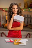 Concerned Young Housewife Holding Letter In Christmas Decorated