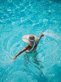 Young woman in bikini wearing a straw hat at the swimming pool