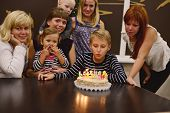 stock photo of niece  - boy and his family in his birthday in light of candles - JPG