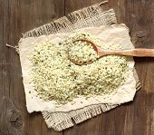 stock photo of spooning  - Hemp seeds with a spoon on a wooden table - JPG