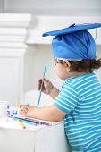 Little boy in blue graduation hat boy with paint and brush in hand at table