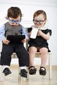 image of lurex  - Little boy with tablet computer sitting on white chair next to happy girl with glasses and mobile phone - JPG
