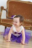 Happy little girl in purple skirt sitting on floor near sofa