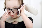 pic of lurex  - Portrait of little girl in black glasses talking on mobile phone  - JPG