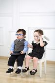 Two little kids in glasses sitting on white chairs: boy with tablet computer, a girl talking on the mobile phone