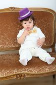 Little boy in white suit and purple hat sitting on couch