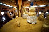 Buddhist Monk worship Five small golden Buddhas.