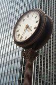 Street Clock In Front  Of A Glass Skyscraper