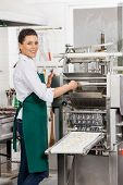 Portrait of smiling female chef processing ravioli pasta in machine at commercial kitchen
