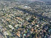 An image shot from an airplane shows what a neighborhood of homes looks like from an elevated perspective.