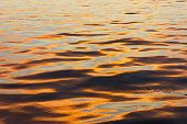 A low, orange sunset reflects off the surface of the ocean, creating a beautiful wavy, natural pattern