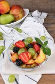 fresh tasty fruit salad on wooden table