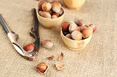 Hazelnuts in wooden bowls, on napkin on sackcloth background
