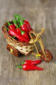 Red hot chili peppers in decorative wicker basket on wooden background