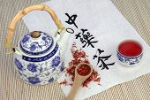 Safflower herb tea also used in chinese herbal medicine, with teapot, cup and calligraphy script on rice paper. Translation reads as chinese herbal tea.