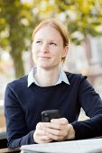 Thoughtful Businesswoman With Smartphone