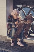 Little girl in a pink beret holds a toy bear