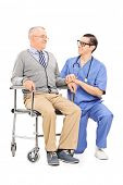 Male nurse talking to a senior patient seated in a wheelchair isolated on white background