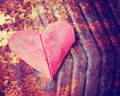 stock photo of discard  -  a discarded paper heart on a rusty background with leaves toned with a retro vintage instagram filter effect  - JPG