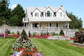 picture of cape-cod  - Summertime flower beds and a detached white house - JPG