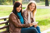 Two young girls sitting in the park and using digital tablet.