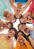 friendship, youth, gesture and people - group of smiling teenagers in circle shouting