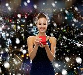 holidays, people and christmas concept - smiling woman in dress holding red gift box over snowy night city background