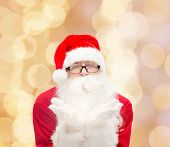 christmas, holidays and people concept - man in costume of santa claus blowing on palms over beige lights background
