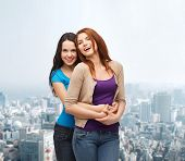 happiness, friendship and people concept - smiling teenage girls hugging over city background