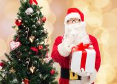 christmas, holidays and people concept - man in costume of santa claus with gift box and tree making hush gesture over beige lights background