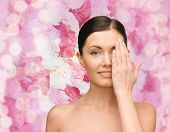 beauty, people and health concept - smiling young woman covering half of face with hand over pink lights background