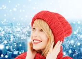 happiness, winter holidays, christmas and people concept - smiling young woman in red hat and scarf over blue snowy background