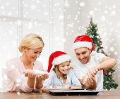food, family, happiness, cooking and people concept - smiling family in santa helper hats glazing cookies on pan over living room and christmas tree background