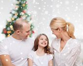 family, childhood, holidays and people - smiling mother, father and little girl over living room and christmas tree background