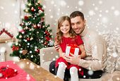 christmas, holidays, family and people concept - smiling father and daughter holding gift box and hugging at home