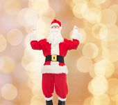christmas, holidays and people concept - man in costume of santa claus having fun over beige lights background