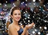 people, holidays, christmas and glamour concept - smiling woman in evening dress with diamond over snowy night city background