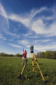 foto of cartographer  - Land Surveyor working with robotic station  - JPG