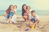 Two Young Mothers And Their Children Having Fun On The Beach