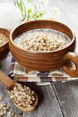 foto of porridge  - Buckwheat porridge with milk in the bowl on the table - JPG