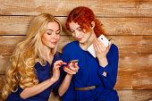 foto of redhead  - Two sisters a blonde and a redhead listening to music on headphones - JPG