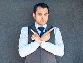 image of opposites  - Closeup portrait of young business man thinking daydreaming pointing opposite directions looking confused isolated gray background - JPG